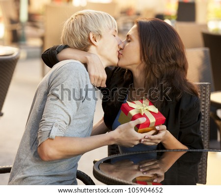 The young man gives a gift to a young girl in the cafe and they are kissing. - stock photo