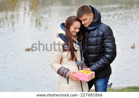 The young man gives a gift to a young girl in the park. - stock photo