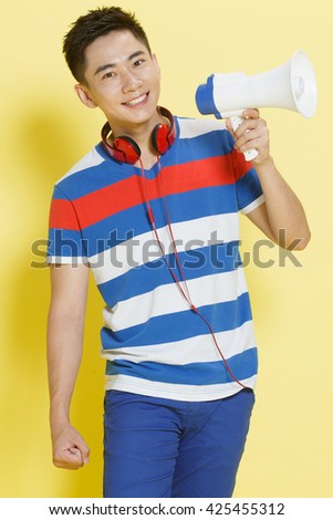 The young man holding a megaphone - stock photo
