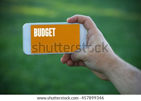The young man holds the hand Budget by smartphone - stock photo