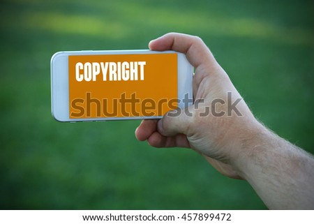 The young man holds the hand Copyright by smartphone - stock photo