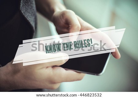 The young man holds the hand Know The Rules! by smartphone - stock photo