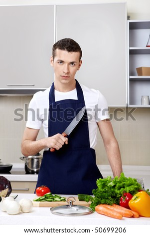 The young man in an apron with a knife at kitchen - stock photo