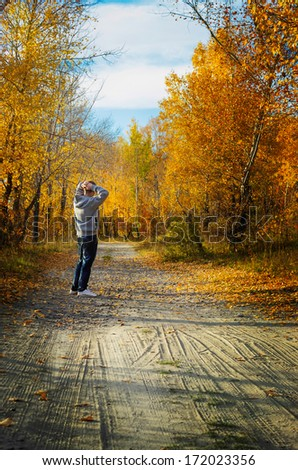 The young man in the autumn wood enjoys beauty