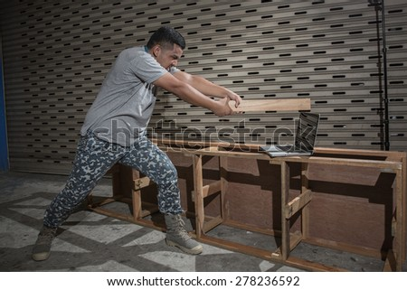The young man is destroying a laptop in anger,The concept of anti-technology - stock photo