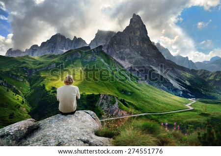 The young man is resting on the rock after hiking trip, he is looking to green mountains meadows under towering hill in italian Dolomite. - stock photo