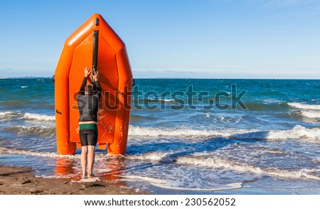 The young man lifeguard is pushing rescue rubber boat on the sea, concept of security on beach.