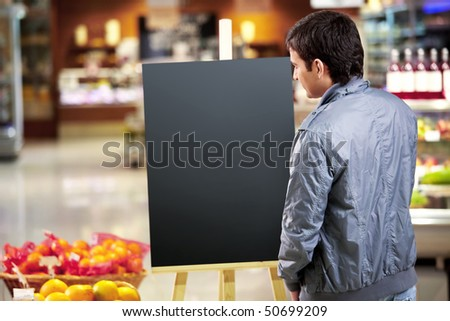 The young man looks at an empty board in shop - stock photo