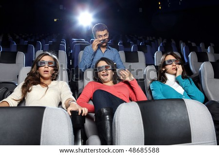The young man observes of the attractive girl at cinema - stock photo