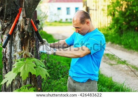 The young man repairs a fence outdoor. - stock photo