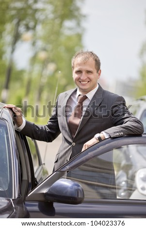 The young man sits down in the car - stock photo