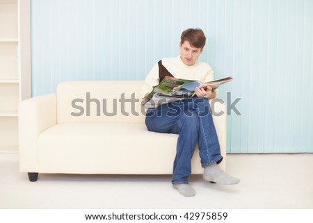 The young man sits on a sofa with the journal - stock photo