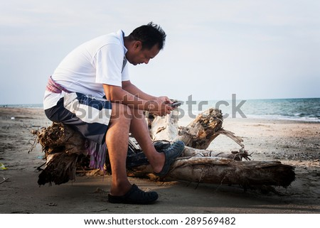 the young man sitting on the timber at the beach and play internet on the smart phone - stock photo