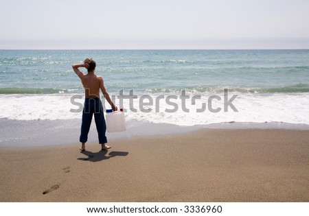The young man stands at the sea and holds in a hand the empty canister for water.Fun.