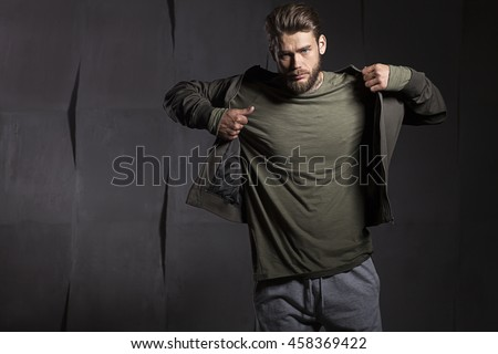The young man takes off his jacket on gray cement background