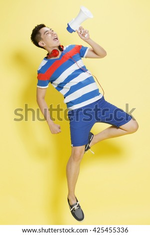 The young man with a megaphone shouting - stock photo