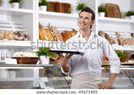 The young man with a tray on a forward background ( - stock photo