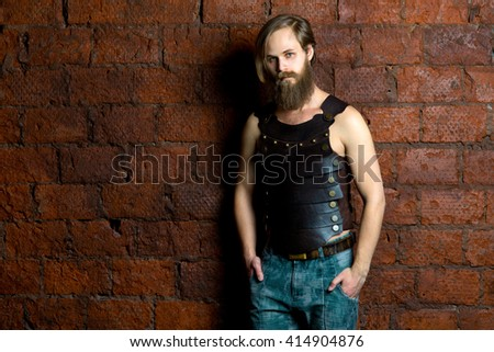 The young man with long hair costs at a red brick wall in a leather vest and jeans