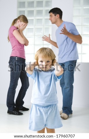 The young marriage quarreling. Theirs daughter stops her ears. Focused on young girl. - stock photo
