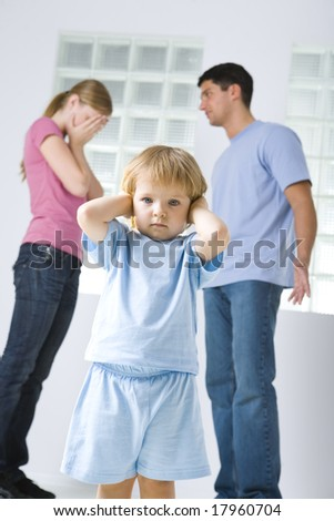 The young marriage quarreling. Theirs daughter stops her ears. Focused on young girl. Low angle view. - stock photo