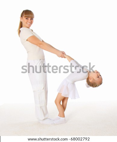 The young mom and her little daughter doing exercises together.