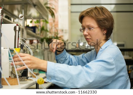 The young nice woman-scientist work with syringe on a background scientific instruments - stock photo