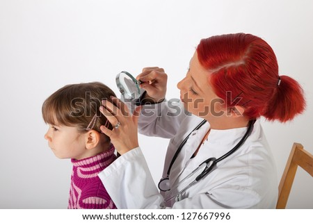 The young pediatrician examines the head of a little girl
