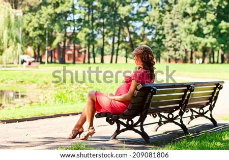 The young pregnant woman has a rest on a bench in park - stock photo