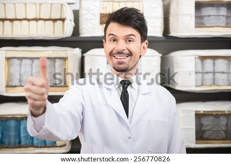 The young salesman is showing quality mattresses in the store. - stock photo