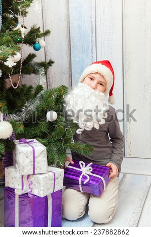 The young Santa Clause sits under the Christmas tree with new year presents - stock photo