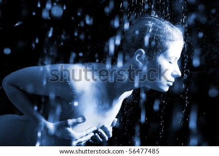 The young sexual woman in splashes of water. Flying drops. Water studio photo.