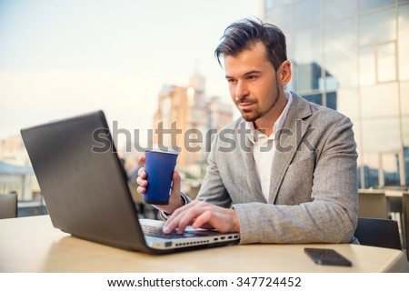 The young successful businessman, sitting at a table in his office using laptop - stock photo