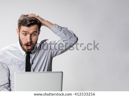 The young surprised man with his laptop computer - stock photo