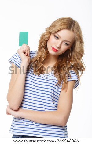 The young thoughtful woman, holding the card of the blank credit near the head, on a white background - stock photo
