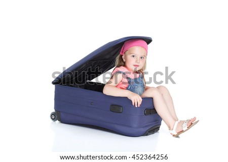The young traveler  girl with blue suitcase. child  inside suitcase ready for travel.  Isolated over white background