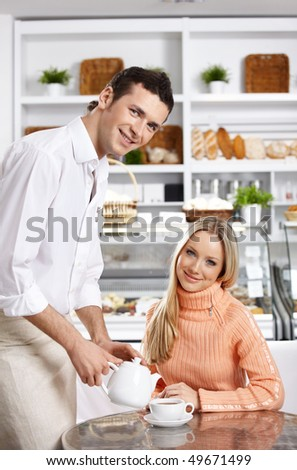 The young waiter pours tea to the attractive girl - stock photo