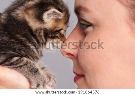 The young woman and little kitten adjoin noses over grey background close-up - stock photo