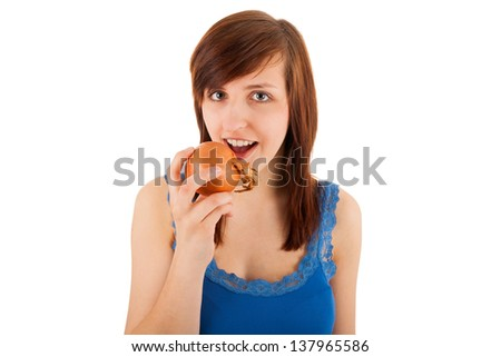 The young woman bites into an onion