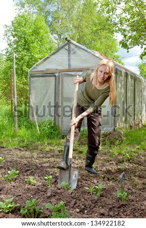 The young woman couch a bed with the first sprouts of potato on a summer cottage - stock photo