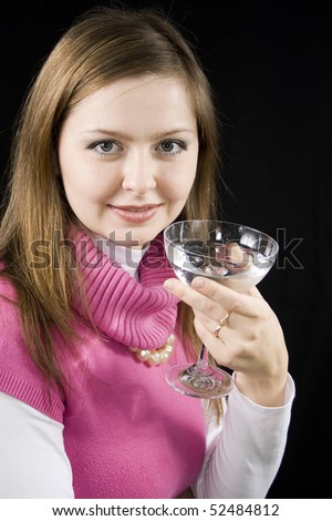 The young woman drinks water from a glass the black background