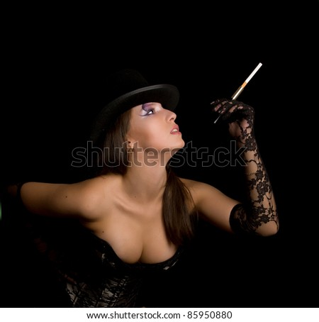 The young woman in a black corset smoke cigarette and looks up - stock photo