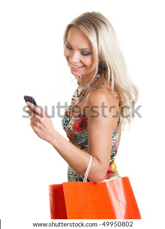 The young woman in elegant clothes looks at a mobile phone - stock photo
