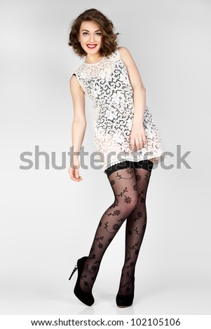 The young woman in white dress on grey background. - stock photo