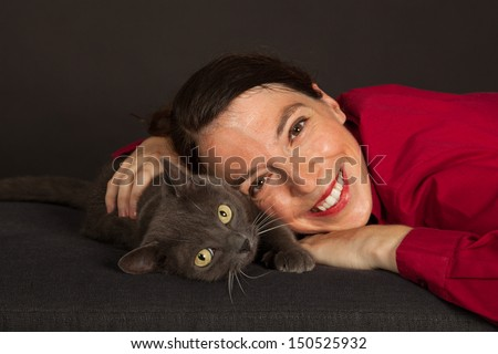 The young woman is cuddling with her cat