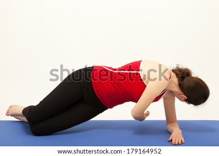 The young woman is exercising on a mat - stock photo