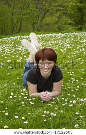 The young woman lays on a grass in park