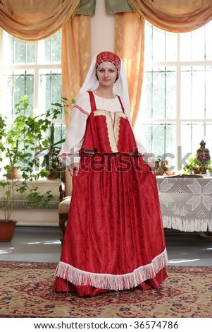 The young woman poses in red dress at home - stock photo