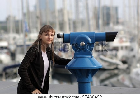 The young woman poses with telescope at summer - stock photo