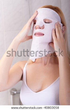 The young woman puts a nutritious mask for the person