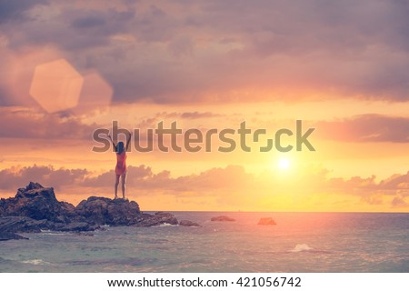 The young woman raised her hand up to the sun, against the sea, rocks and sky with clouds - stock photo